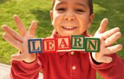 smiling child holding blocks that say learn